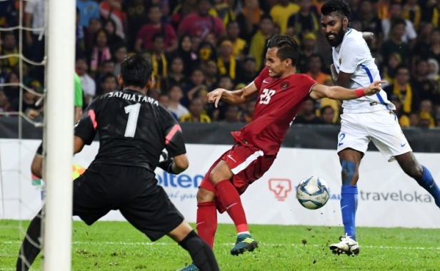 Thanabalan Nadarajah (R) of Malaysia vies for the ball with Muhamad Rezaldi Hehanusa (C) of Indonesia during their semi-final football match at the 29th Southeast Asian Games (SEA Games) in Kuala Lumpur on August 26, 2017. / AFP PHOTO / ADEK BERRY